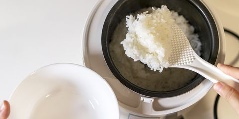 spooning rice from electric cooker