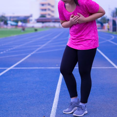 sport girl having heart attack or chest pain after jogging or running work out on running track sport and health care concept