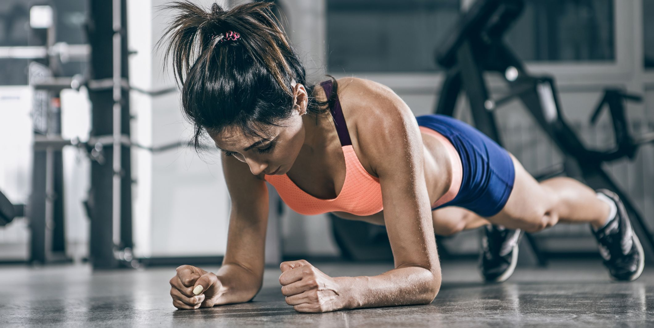 Sport. Muscular woman on a plank position.