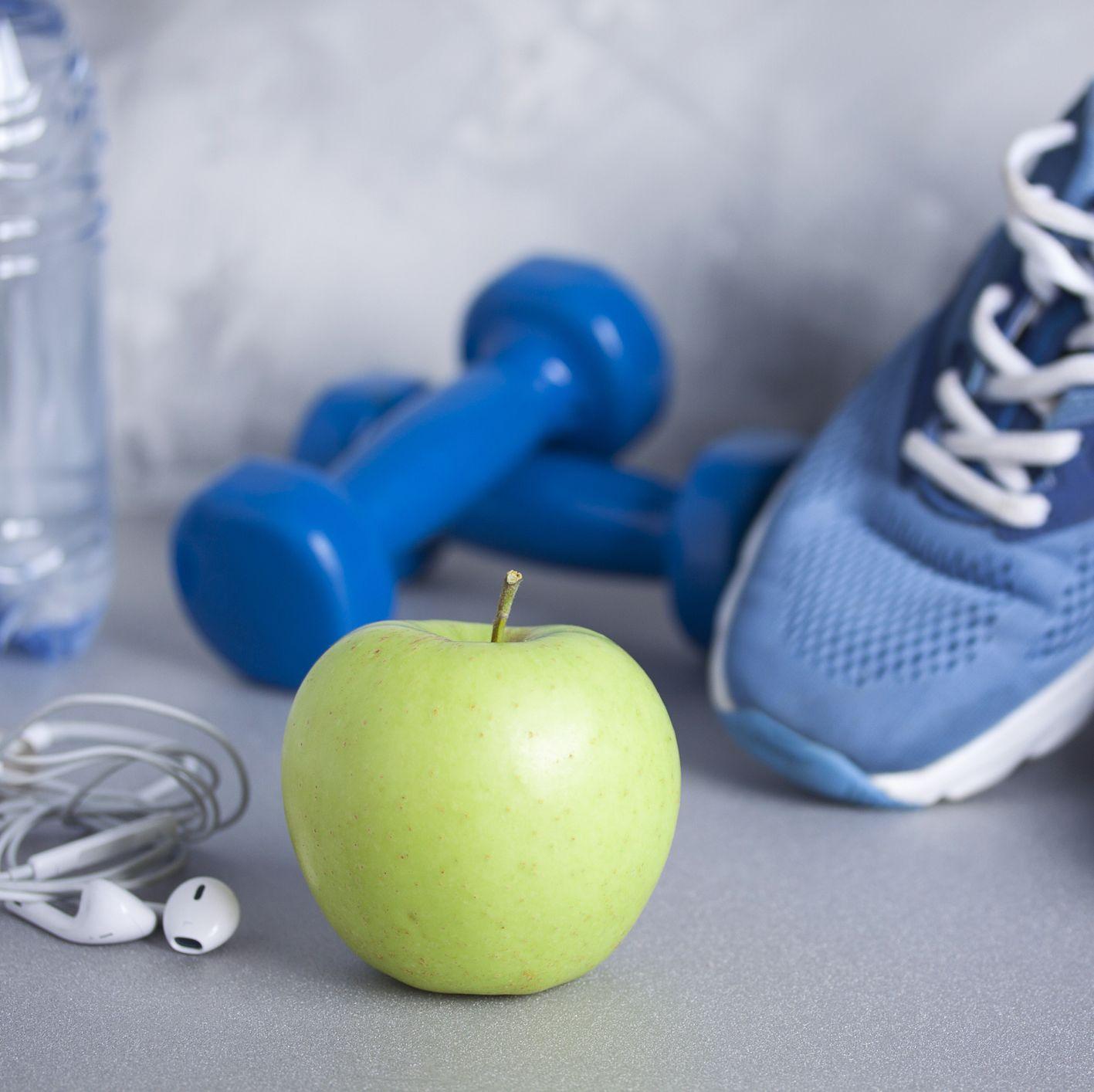 Sport shoes, dumbbells, earphones, apple, bottle of water, concrete background