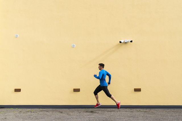 sportive man running along yellow wall with cctv camera