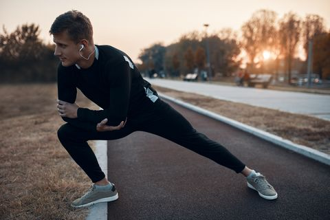 sportive man stretching in the evening