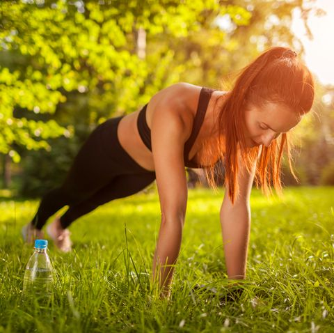 sportive woman doing plank exercise outdoor in summer park motivation healthy lifestyle