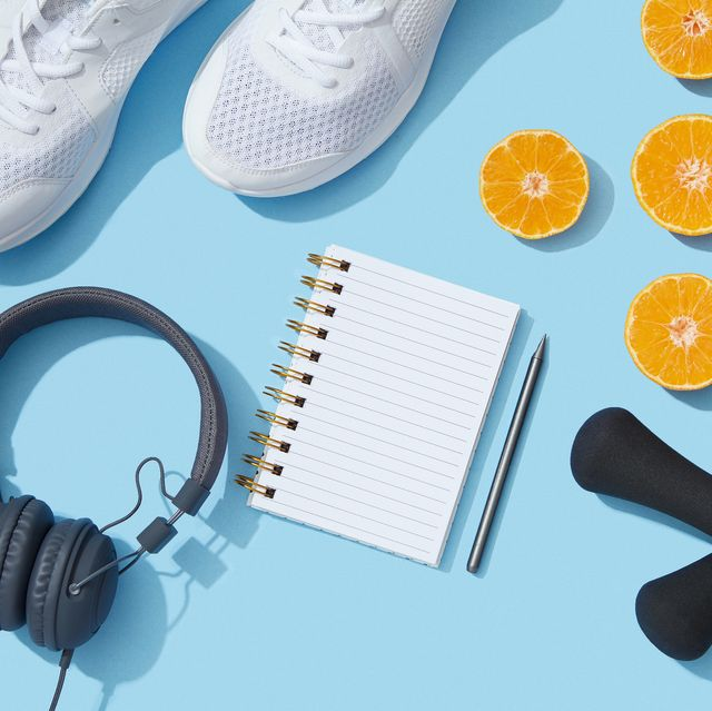 sports equipment and accessories, shoes, dumbbells, notebook and oranges on blue background