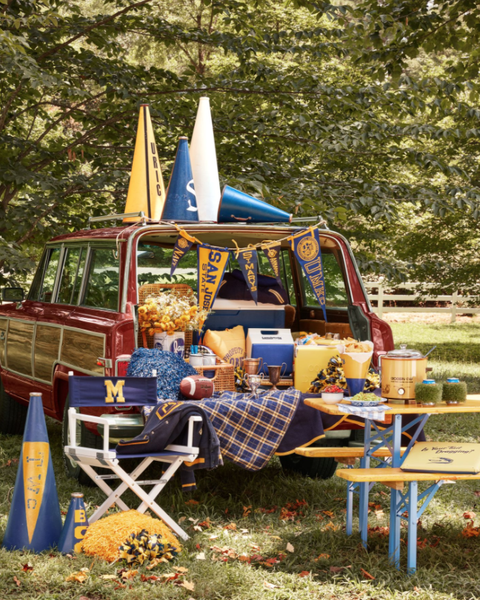 a woody wagoneer styled in yellow and blue for a football tailgate