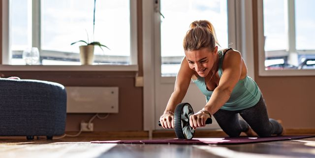 sports woman is doing ab roller exercise while working out