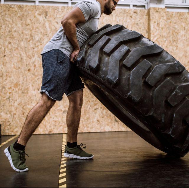 Sportsman Pushing Tire On Cross Training In Gym