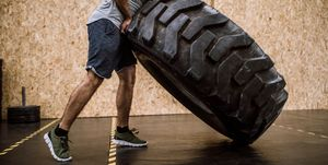 Sportsman Pushing Tire On Cross Training In Gym