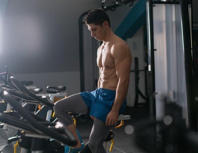 sportsman riding stationary bicycle in gym