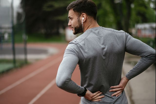 sportsman suffering from backache at park outdoors