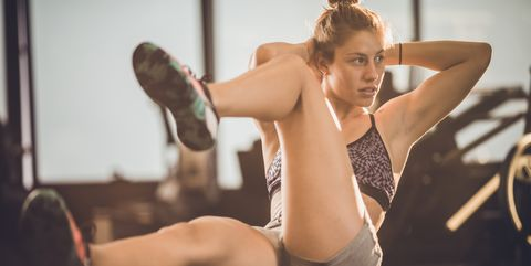 Sportswoman doing abs workout during sports training in a health club.