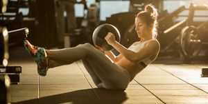 Sportswoman doing sit-ups with medicine ball on sports training in a gym.