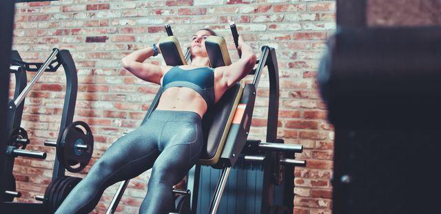 woman doing hack squats at gym