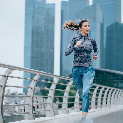 Sportswoman running on bridge