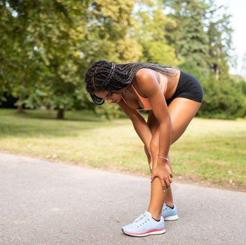 sportswoman suffering from leg cramp due to overtraining
