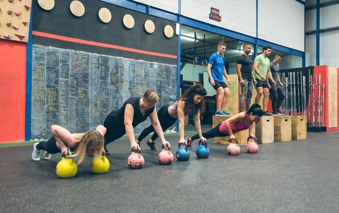 sportswomen training with kettlebells and sportsmen doing box jumps