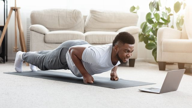 sporty black man making fist plank exercise in front of laptop