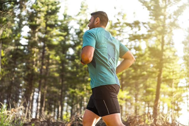 sporty mid adult man jogging against trees