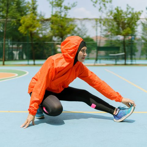 sporty muslim woman and runner with hijab stretching legs in the park