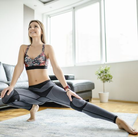 sporty woman doing relaxation exercises after intensive training at home