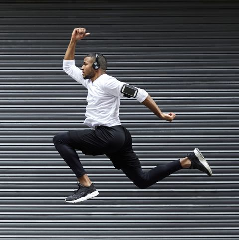 Sporty young man jumping against shutter