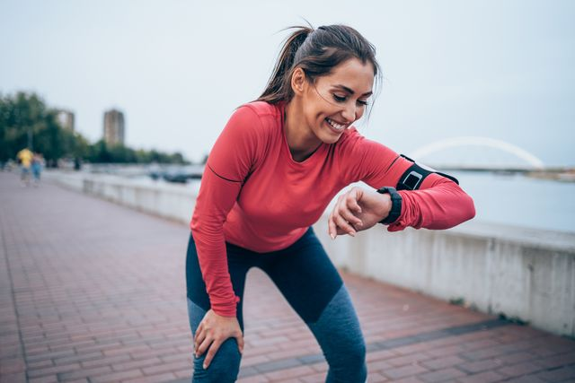 sporty young woman checking the time after jogging