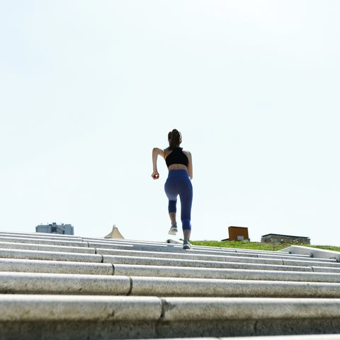 Sporty young woman running up staircase