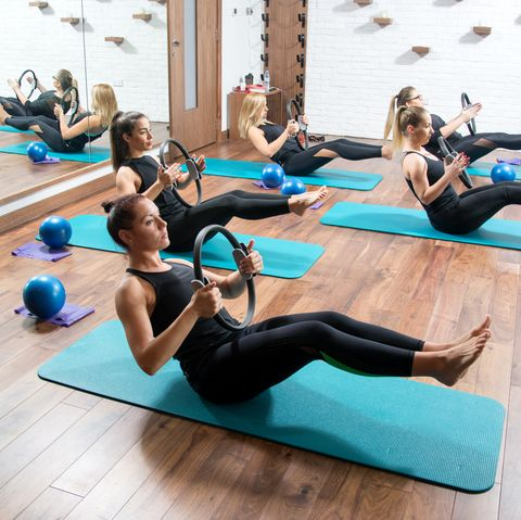 Sporty young women with exercising rings in fitness studio.