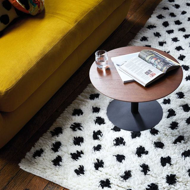 black and white spotted hand woven wool rug, yellow mustard velvet sofa and small wooden sidecoffee table with magazine and a glass of water