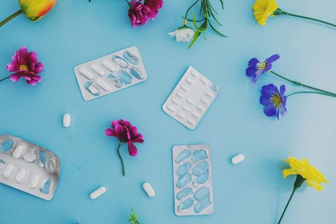spring allergy concept  with pills and flowers