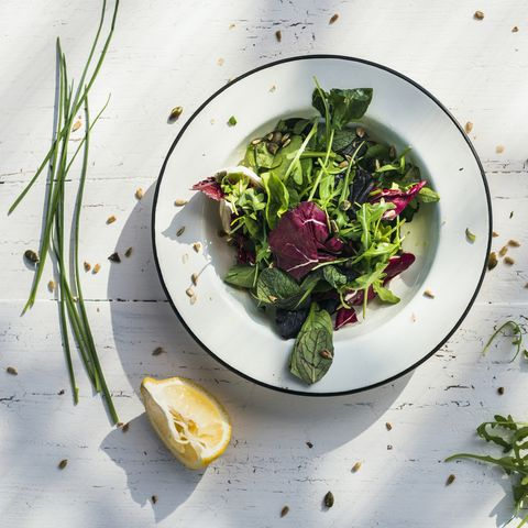 spring salad of baby spinach, herbs, arugula and lettuce on plate, lemon
