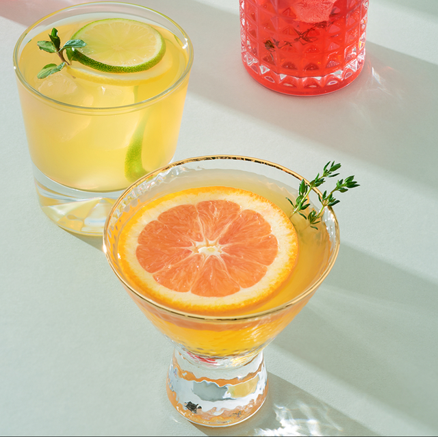 a group of cocktail glasses filled with orange, yellow, and red cocktails