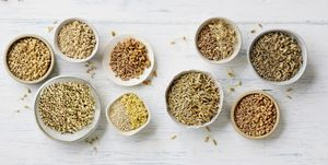 Sprouted and unsprouted grains in bowls on whitewashed wood background