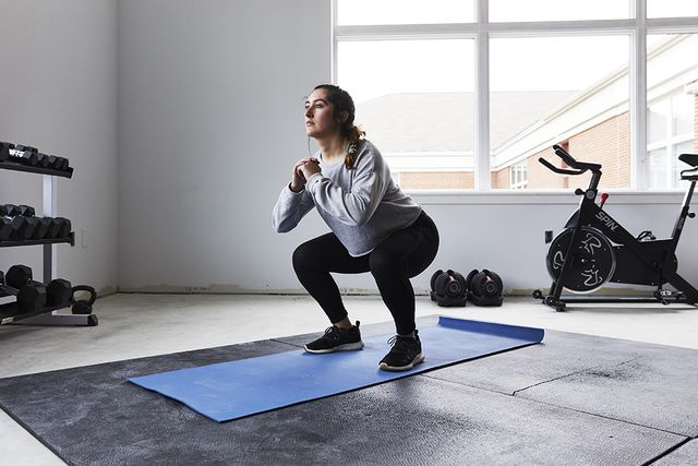 young woman squats in home gym