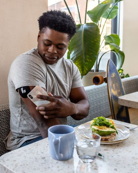 man measuring his glucose levels with app at table at restaurant