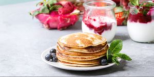Stack of homemade pancakes served on plate with berries, mint, glass jars of yogurt, bottle of lemonade, fruit salad in pink dragon fruit over grey texture table