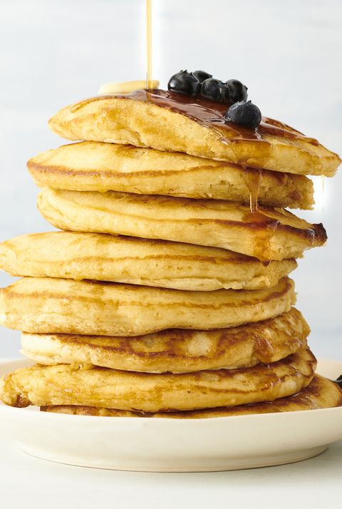 stack of pancakes with blueberries and maple syrup in plate on table