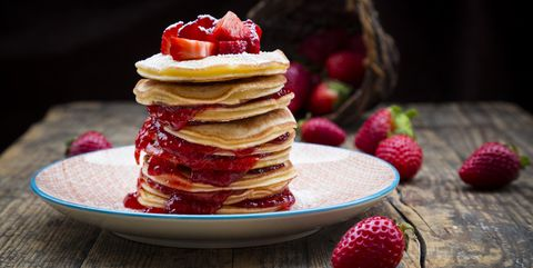 Stack of pancakes with strawberry sauce and strawberries