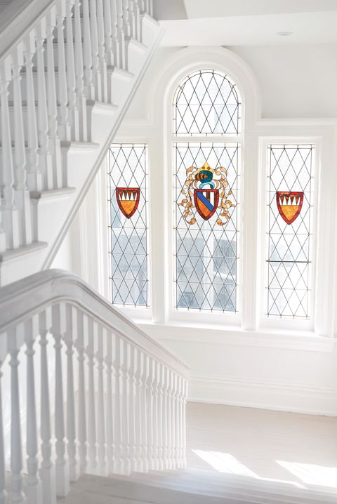 white hallway with stained glass windows of crest