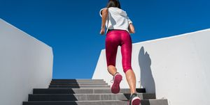 Stairs running woman doing run up on staircase - female runner