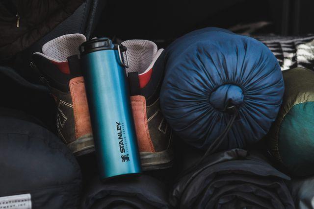 a blue insulated mug next to hiking boots