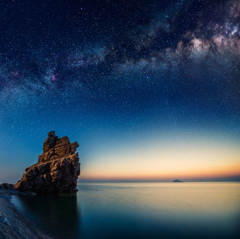 Starry night over rock formations by the Pacific Ocean