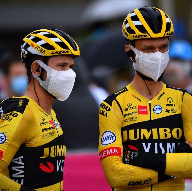 riders from team jumbo visma wearing masks