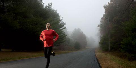 Man Running Down Dark Misty Road