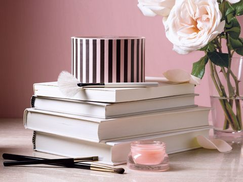 Beauty Products on stacked books with flowers