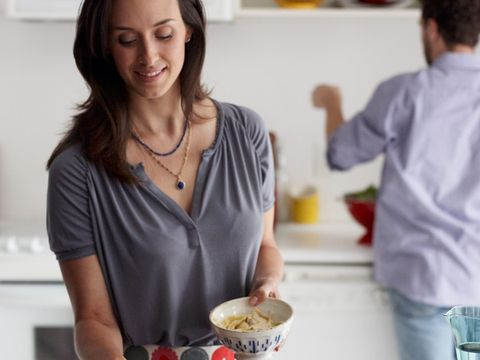 Man helping woman cook a meal