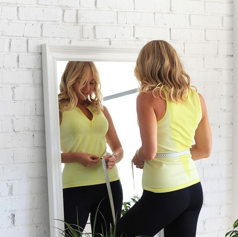 stay in shape young woman with athletic body measures her waist with a measure type in front of a mirror