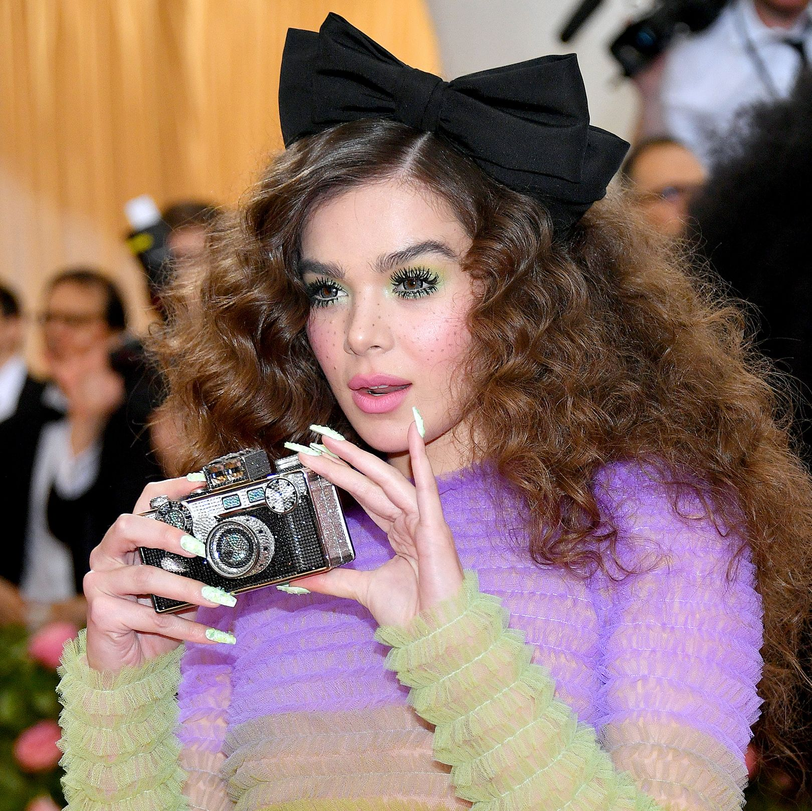 Hailee Steinfeld Steinfeld looked like a doll in Twiggy-like lashes, lime green eyeshadow, and super bright pink lips and cheeks. Her curls, styled with an oversized black bow, looked super fluffy.