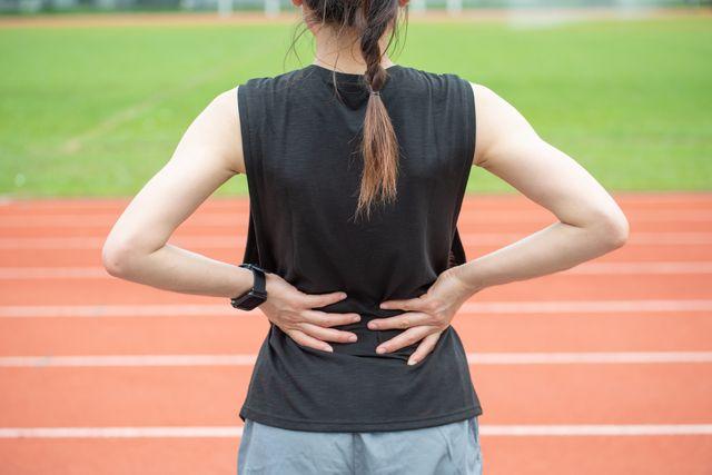vrouw op atletiekbaan heeft last van steken in zij