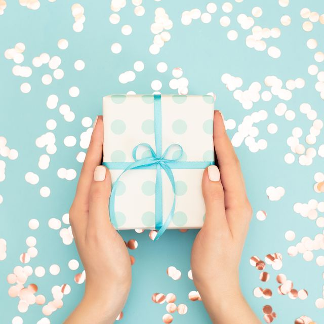 Womans hands holding gift or present box decorated confetti on pink pastel table top view. Flat lay composition for birthday or wedding.